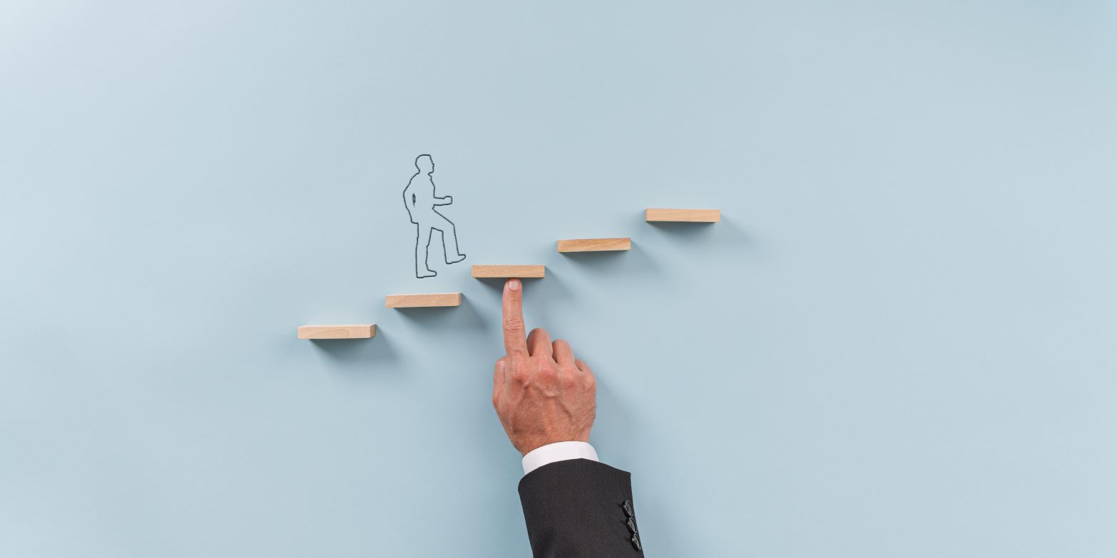 hand of businessman supporting wooden step for silhouetted man to walk upwards Toni García CEO Millennial Inmobiliario